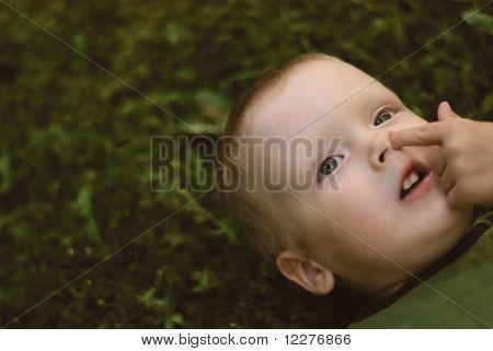 A Little Boy Lying On Grass