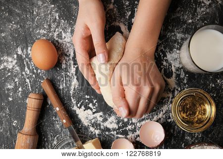 Female hands kneading dough, top view