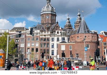 AMSTERDAM - APRIL 27: Amsterdam cityscape on King's Day with St. Nicolas church and Schreierstoren (Weeper's Tower) in the background people in orange go to take part in festival on April 27, 2015.