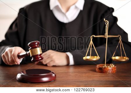 Judge hitting gavel at wooden table closeup