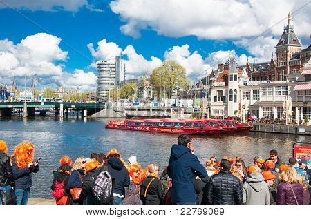 AMSTERDAM - APRIL 27: People on the river front wait for the boat to take part in celebrating King's Day on April 27, 2015 the Netherlands. The King Day is celebrated every year in April 27.