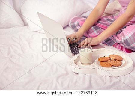 Woman in pajamas using a laptop on her bed