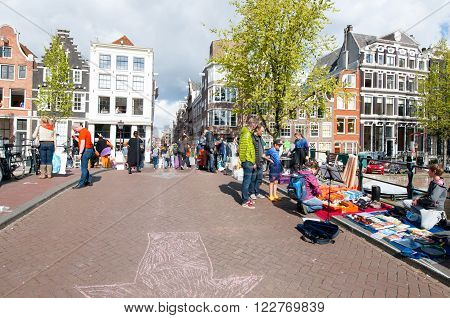 AMSTERDAMNETHERLANDS-APRIL 27: Local people display their things for sale on King's Day on April 27 2015 in Amsterdam Netherlands.