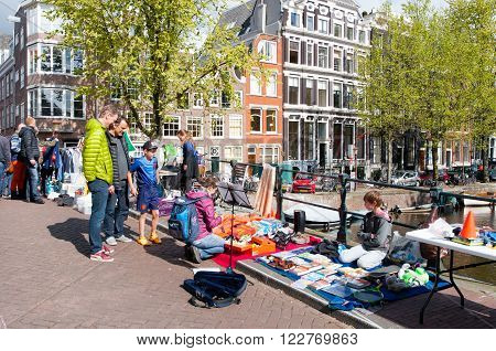 AMSTERDAMNETHERLANDS-APRIL 27: Locals display their old things for sale on King's Day on April 27 2015 in Amsterdam Netherlands.
