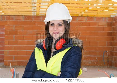 Smiling woman working on a construction site crossed arms