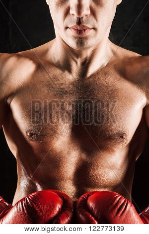 The young male athlete kickboxer on a black background