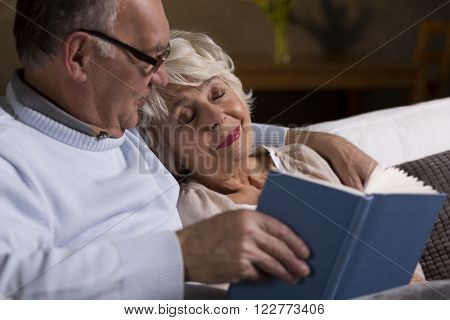 Cropped picture of an ederly couple reading a book
