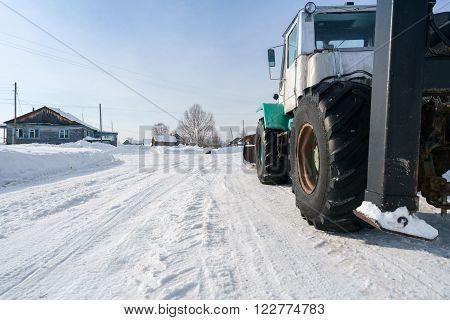 Tractor rides through village in winter, close-up