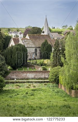 View of All Saints church in the village of Loose Kent UK with orchards and farmland in the distance