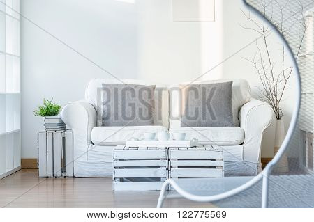 Light interior with sofa, DIY small table and comfortable, white chair