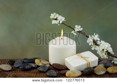 apple tree blossoms with stones candle on mat