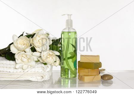 Set of massage oil and stones, towel, gardenia