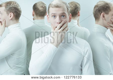 Duplicated image man with surprised face, covering mouth with his hand, standing in light interior