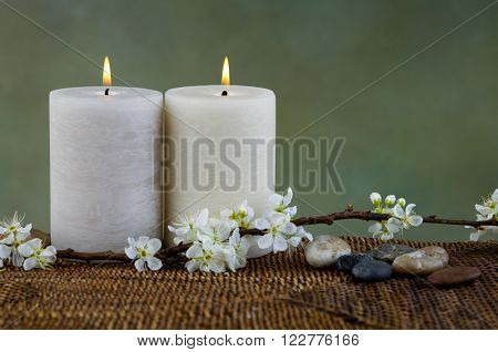 Beautiful crab apple tree blossoms with stones candle on mat