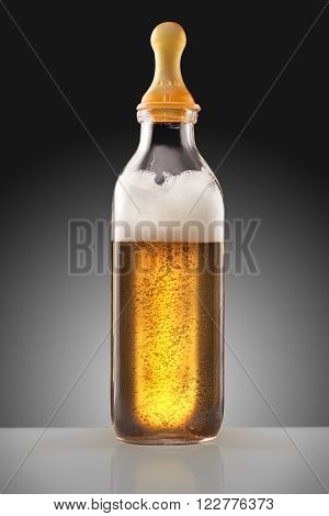 A feeding bottle with nipple full of beer as a milk replacement for babies.