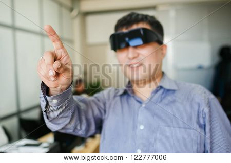 A man in a virtual reality helmet points finger up in the air inside the office premises.