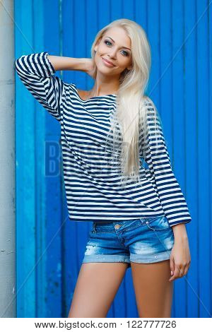 The young beautiful woman, the blonde with a long straight hair and blue eyes, an easy make-up, is dressed in a sea stripped vest and blue jeans shorts, poses in the fresh air in summertime on a blue background