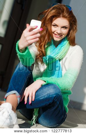 Young beautiful woman with red curly long hair and green eyes,light makeup and pink nail Polish,dressed in a knitted sweater white-green color,the neck is blue-green light scarf,is making selfie on mobile phone in fall city