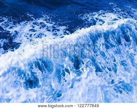 beautiful clear blue sea water flowing seething foaming and splashing white foam spraying sprays and drops