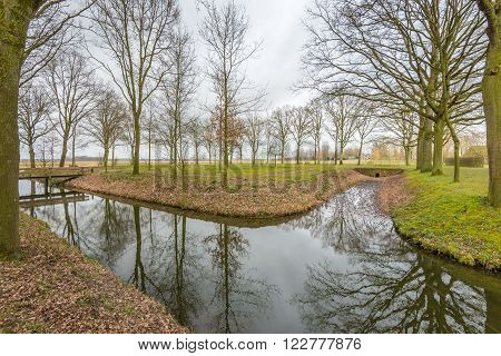 Bare trees reflected in the mirror like surface of a few streams in the park on a cloudy day at the end of the winter season.