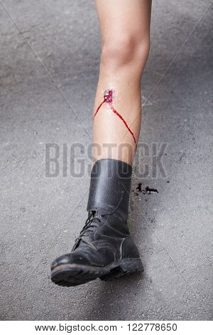 Gunshot wound on soldier's leg. First aid training.