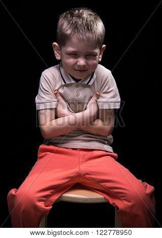 Grimacing smiling little boy on black background