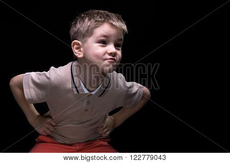 Little grimacing boy with hands on hips on black background