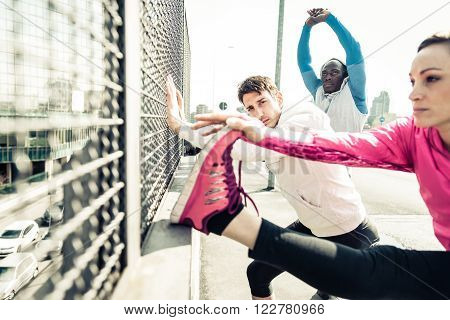 Three multiethnic athletic runners stretching and resting during a workout session in a urban area - Young sportive people getting ready for a run outdoors