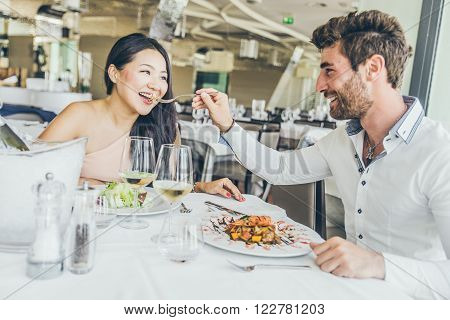 Couple of lovers having a romantic lunch in a restaurant to celebrate anniversary