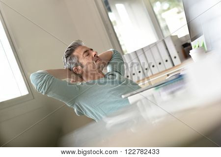 Man in office relaxing and stretching arms