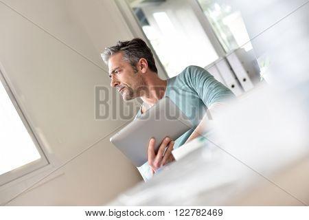 Man in office working on digital tablet
