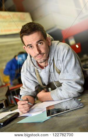 metalworker in workshop reading instructions