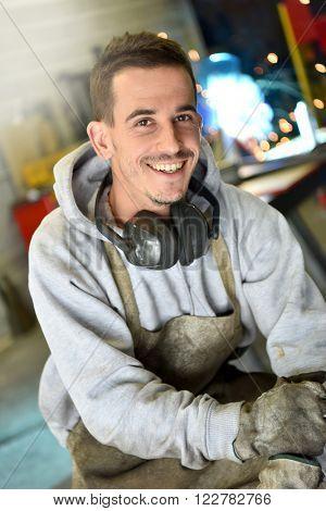 Portrait of happy metalworker in workshop