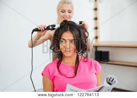 Woman hairdresser making hairdo using curling iron in beauty saloon