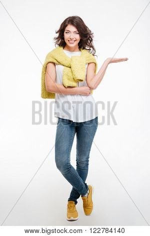 Full length portrait of a happy casual woman holding copyspace on the palm isolated on a white background
