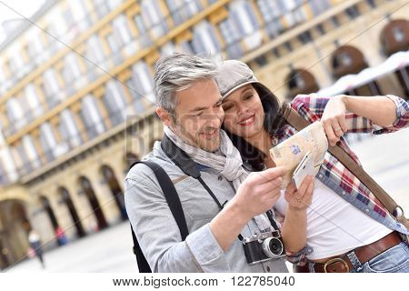 Couple of tourists reading map on historical site