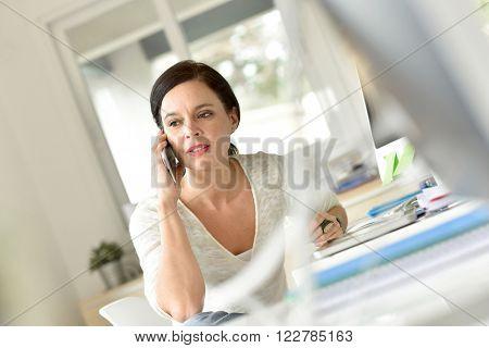 Woman in office talking on phone
