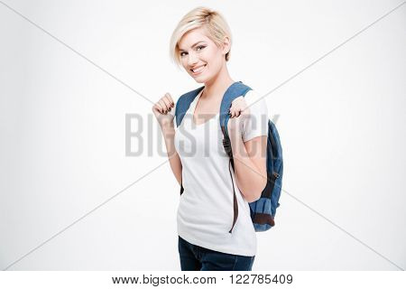 Happy female student with backpack standing isolated on a white background