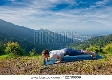 Beautiful sporty fit woman practices Ashtanga Vinyasa yoga Surya Namaskar Sun Salutation asana Chaturanga Dandasana - four-limbed staff pose outdoors in mountains. Himachal Pradesh, India