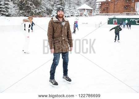 Smiling man ice skating outdoors with snow on background