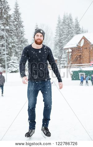 Full length portrait of a handsome man ice skating outdoors with snow on background