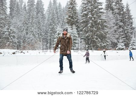 Portrait of a happy young man ice skating outdoors