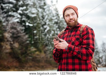 Happy male hiker using smartphone and looking away