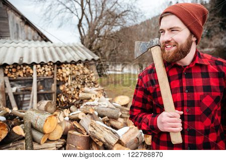 Smiling lumberjack holding axe and looking away outdoors