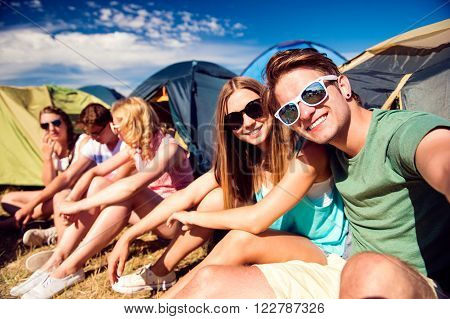 Group of teenage boys and girls at summer music festival, sitting on the ground in front of tents, taking selfie