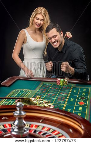 Young couple celebrating win at roulette table in casino. Addiction to the gambling