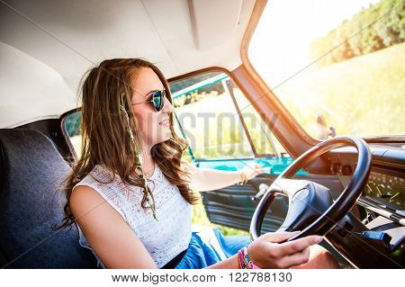 Hipster teenage  girl inside an old campervan driving, roadtrip, sunny summer day