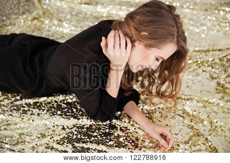 Cheerful attractive young woman lying and looking down over sparkling background
