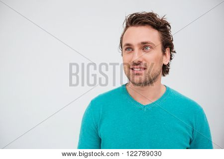 Closeup portrait of happy attractive young man in blue jumper looking up and smiling over white background