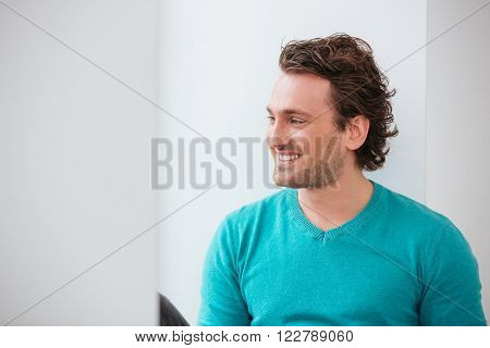 Cheerful young man in blue jumper looking at the window and smiling over white background